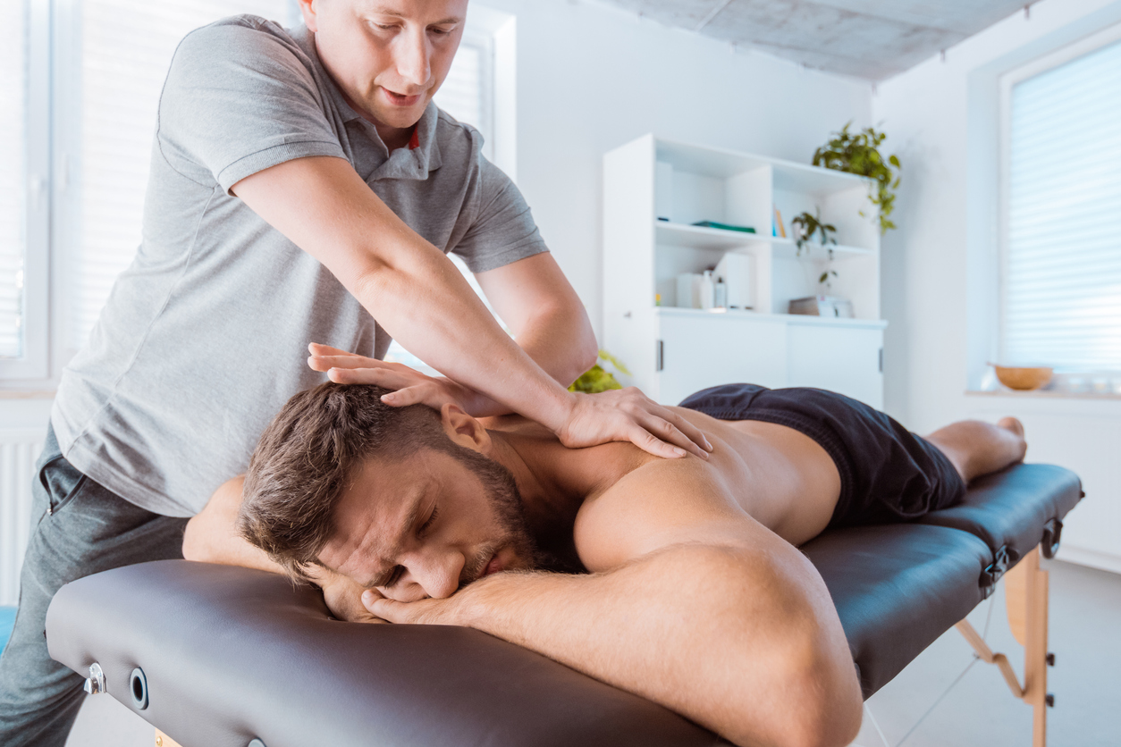 Physical therapist giving back massage to young man. Patient lying down on massage table.